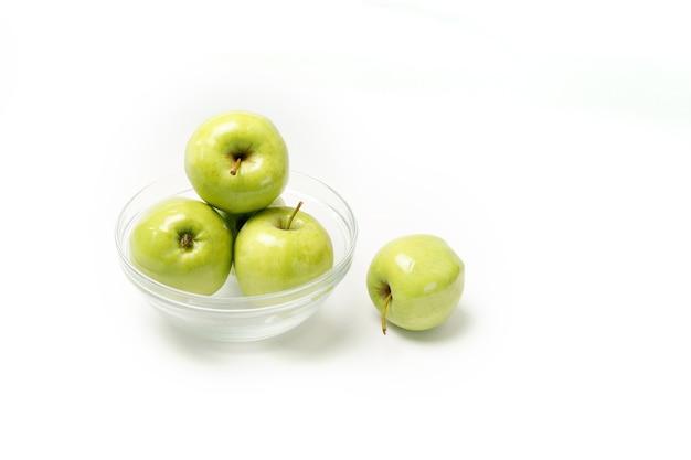 Maçãs verdes em uma placa transparente em um fundo branco. alimentação saudável