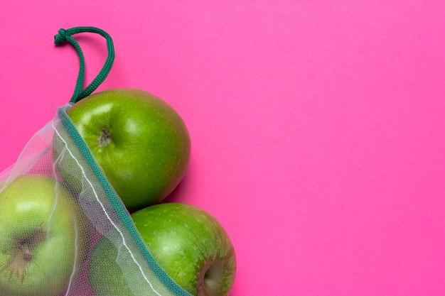 Maçãs verdes em uma sacola ecológica em um fundo rosa
