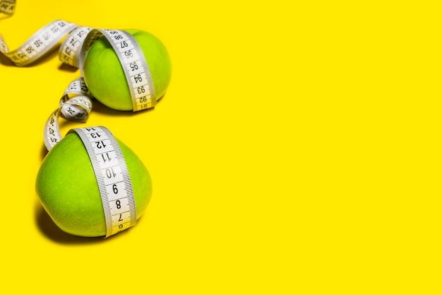 Maçãs verdes embrulhadas com uma fita métrica em um fundo amarelo.