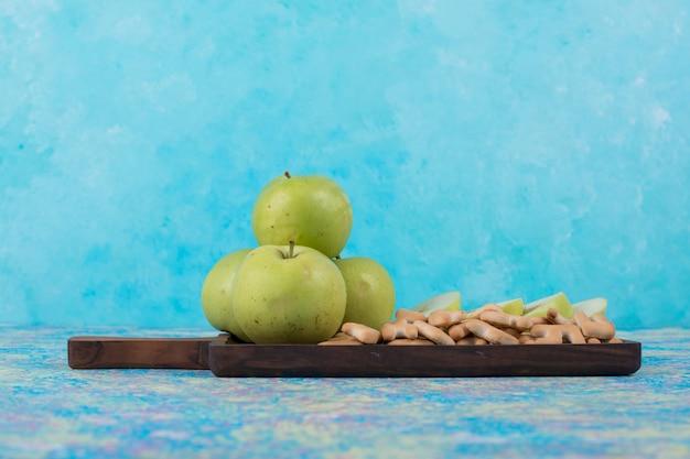 Maçãs verdes fatiadas com biscoitos na placa de madeira em azul.