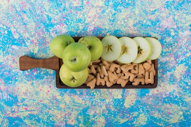Maçãs verdes fatiadas com biscoitos na placa de madeira, no centro