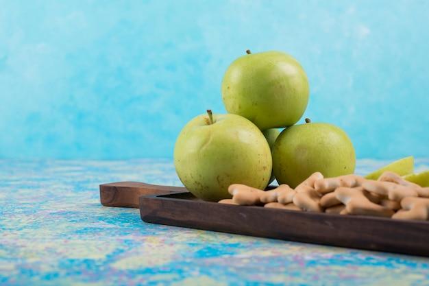 Maçãs verdes fatiadas com biscoitos na placa de madeira, vista lateral