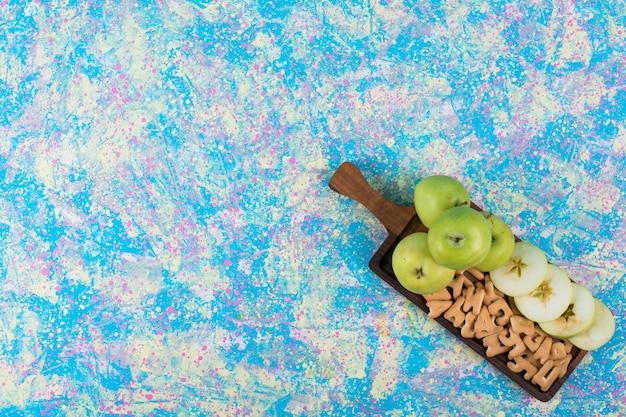 Maçãs verdes fatiadas com biscoitos na placa de madeira, vista superior