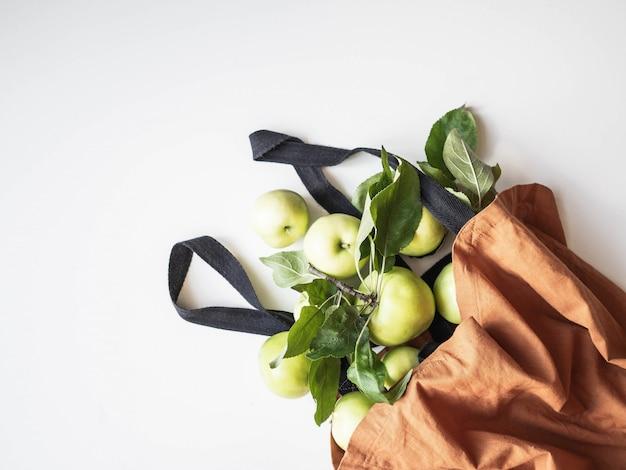 Maçãs verdes frescas com folhas em saco de algodão marrom em fundo branco. vista do topo. copie o espaço
