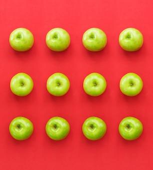 Maçãs verdes frescas em fundo de papel vermelho