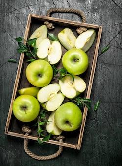 Maçãs verdes frescas em uma bandeja de madeira. sobre um fundo rústico.