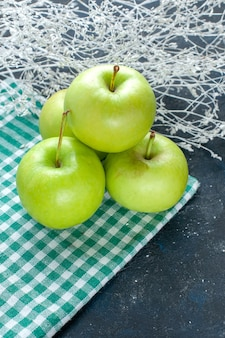 Maçãs verdes frescas maduras e suculentas azedas em azul-escuro