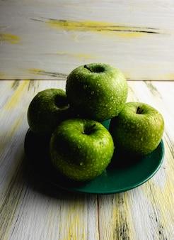 Maçãs verdes frescas na mesa de madeira velha. comida saudável e ecológica. harmonia de cores