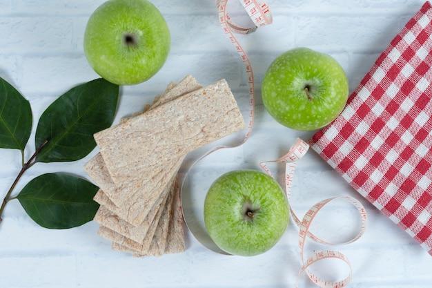 Maçãs verdes inteiras com fita métrica e pão saudável crocante.