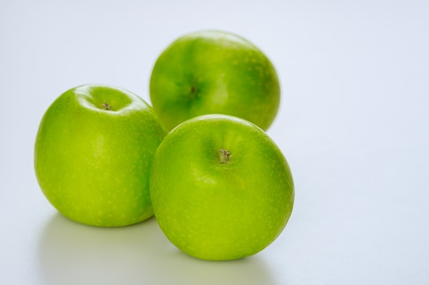 Maçãs verdes inteiras e isoladas no fundo branco. produza o produto.