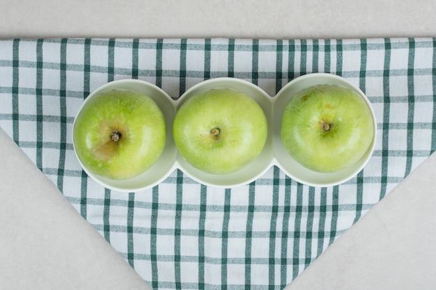 Maçãs verdes inteiras em pratos brancos com toalha de mesa listrada
