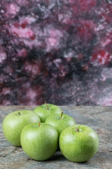 Maçãs verdes isoladas em uma superfície de concreto