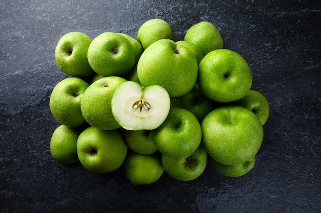 Maçãs verdes maduras com gotas de água em cima da mesa, lindas frutas em um fundo de mármore