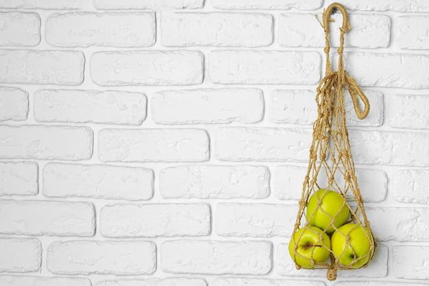 Maçãs verdes maduras em um saco de corda leve