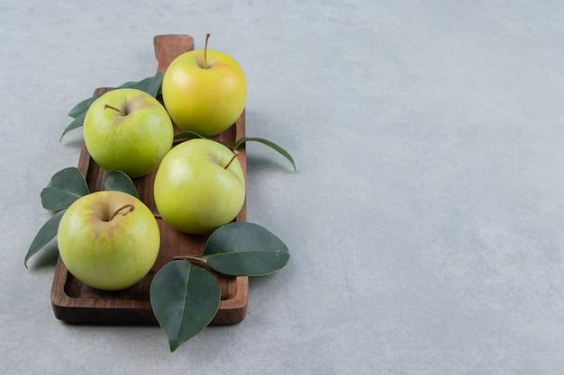 Maçãs verdes maduras na placa de madeira.
