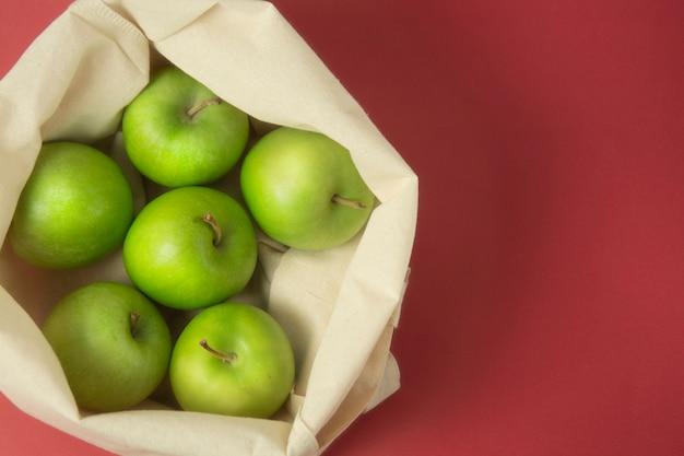 Maçãs verdes na sacola sobre fundo vermelho. zero conceito de desperdício.
