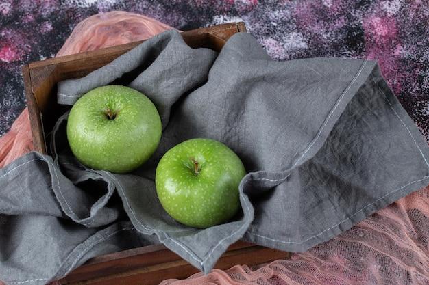 Maçãs verdes na toalha de cozinha cinza.