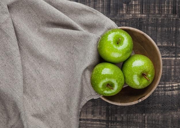 Maçãs verdes saudáveis na tigela de madeira