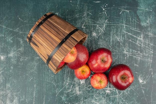 Maçãs vermelhas caindo do balde na mesa de mármore.