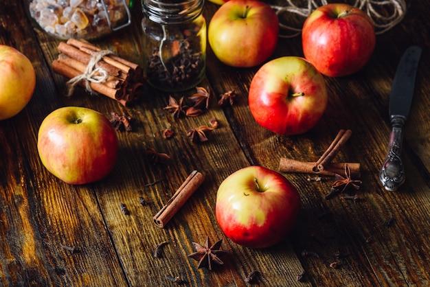 Maçãs vermelhas com especiarias diferentes para cozinhar a torta de maçã.
