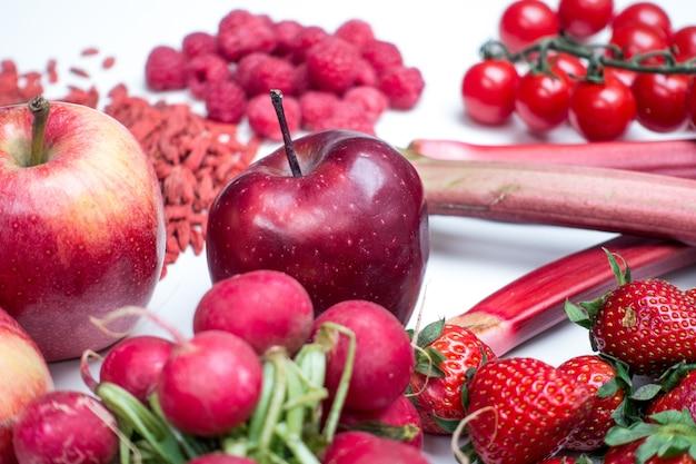 Maçãs vermelhas e outras frutas vermelhas e vegetais em um fundo branco