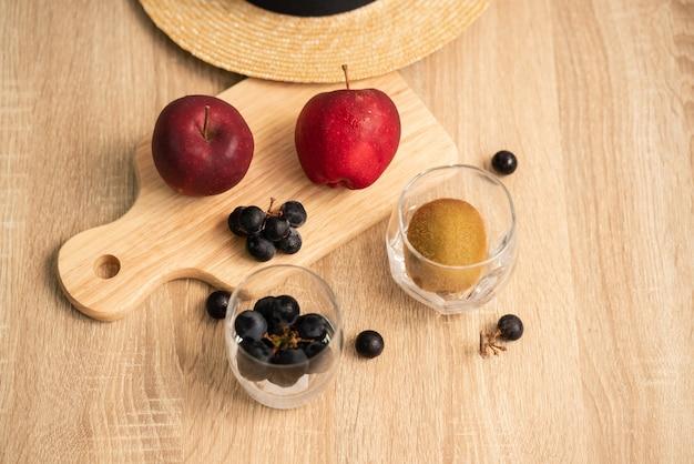 Maçãs vermelhas e um cacho de uvas pretas na placa de madeira, um cacho de uvas pretas e kiwis no chapéu de vidro e palha na superfície da mesa de madeira