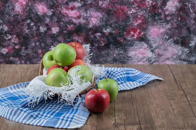 Maçãs vermelhas e verdes em azul toalha de cozinha marcada.