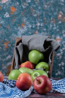 Maçãs vermelhas e verdes fora de uma cesta na toalha marcada.