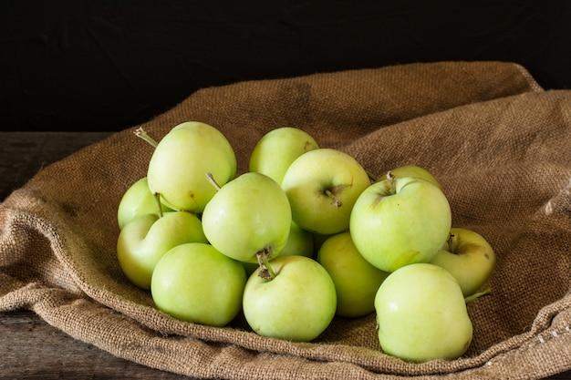 Maçãs vermelhas e verdes maduras no fundo de madeira. maçãs na tigela. frutas do jardim frutas do outono