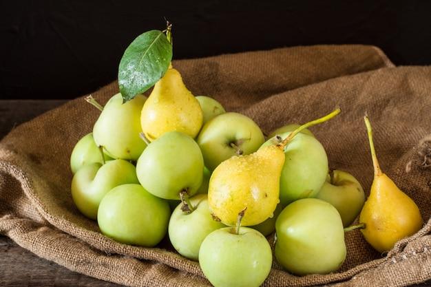 Maçãs vermelhas e verdes maduras no fundo de madeira. maçãs na tigela. jardim. colheita de outono. vós