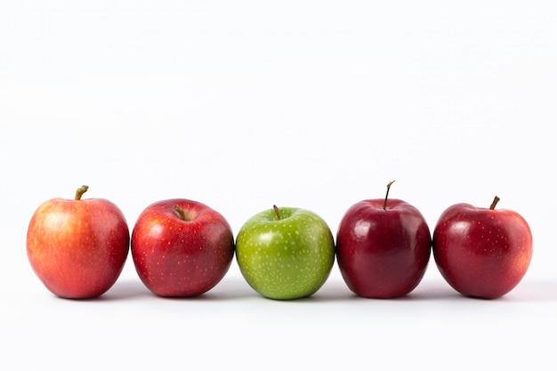 Maçãs vermelhas e verdes maduras suculentas em uma mesa branca