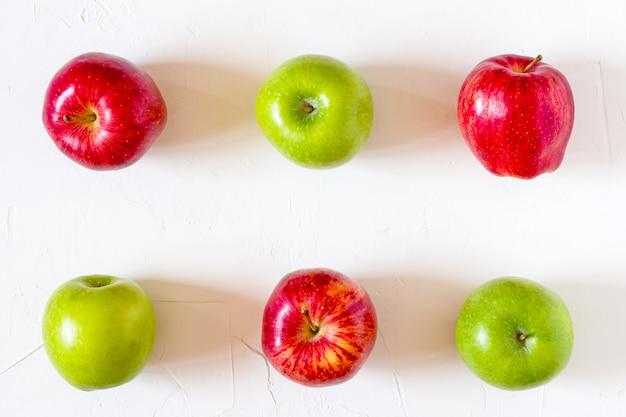 Maçãs vermelhas e verdes na mesa branca.