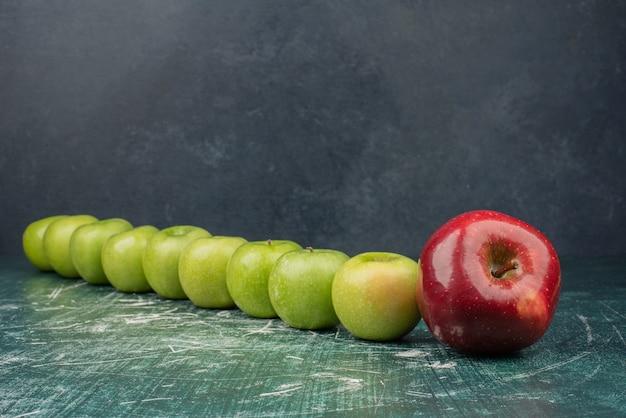 Maçãs vermelhas e verdes na mesa de mármore