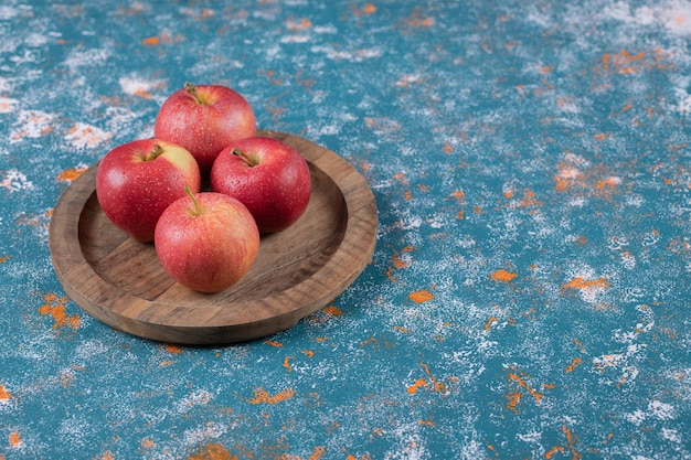 Maçãs vermelhas em uma bandeja de madeira em azul.