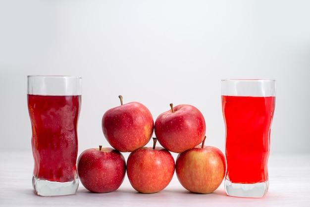 Maçãs vermelhas frescas alinhadas com sucos na mesa branca frutas frescas maduras maduras