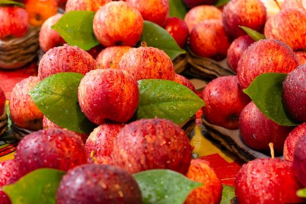 Maçãs vermelhas frescas com folha verde e a gota de água no mercado