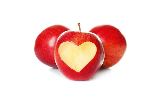 Maçãs vermelhas frescas e uma com recorte em forma de coração no fundo branco
