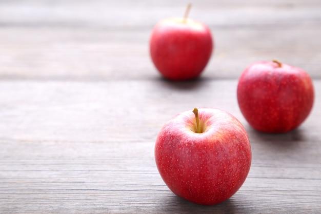 Maçãs vermelhas frescas em um fundo cinza de madeira