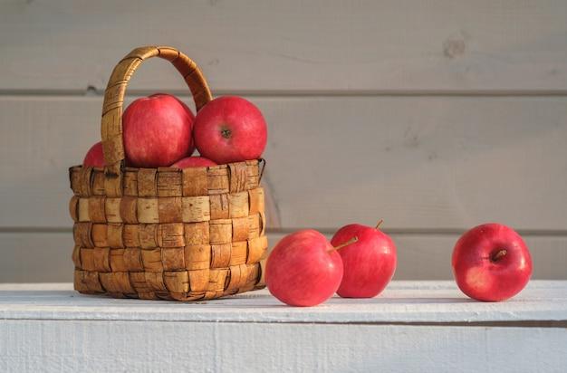 Maçãs vermelhas frescas em uma cesta de vime vintage em uma caixa branca no fundo da parede cinza