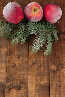 Maçãs vermelhas geladas com galho de pinheiro em fundo de madeira