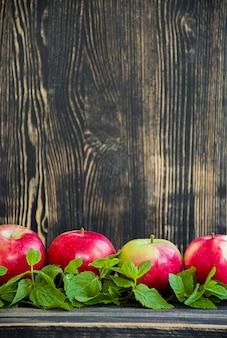 Maçãs vermelhas maduras com hortelã.