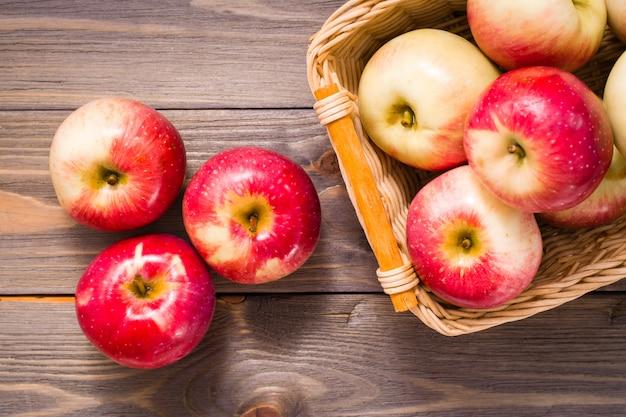 Maçãs vermelhas maduras e cesta com maçãs em uma mesa de madeira. copyspace