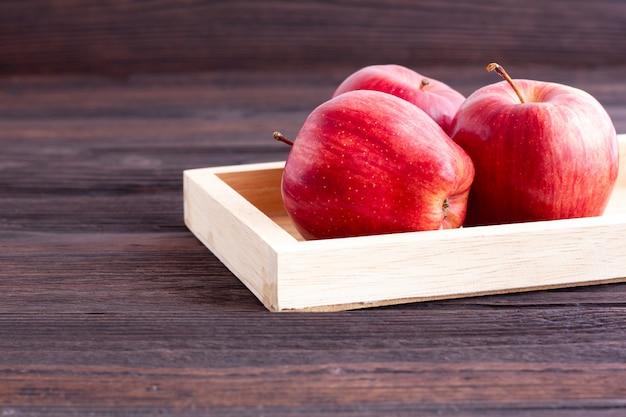 Maçãs vermelhas na mesa de madeira.
