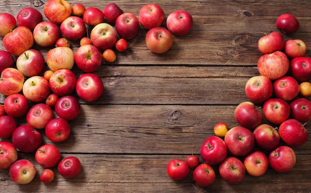 Maçãs vermelhas na velha superfície de madeira