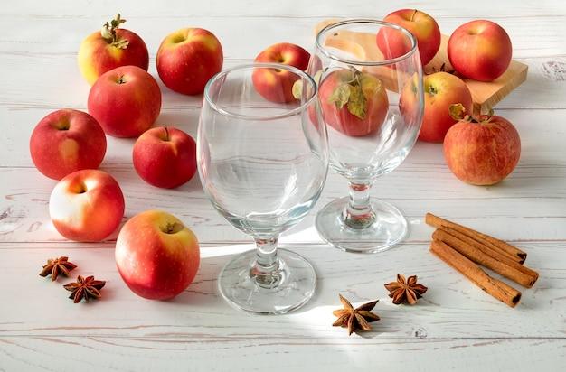 Maçãs vermelhas suculentas frescas maduras, especiarias e copos para cidra numa superfície de madeira clara. orientação horizontal, foco seletivo.