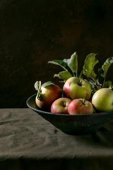 Maçãs vermelhas verdes maduras de jardinagem orgânica com folhas em um prato de cerâmica que está na toalha de mesa escura. fundo preto. colheita de outono. copie o espaço