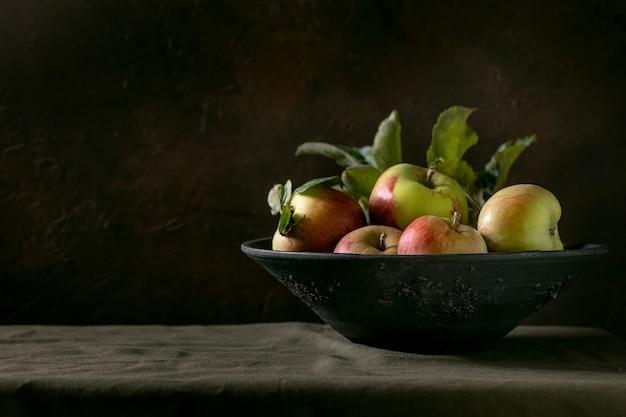 Maçãs vermelhas verdes maduras de jardinagem orgânica com folhas no grande prato de cerâmica que está na toalha de mesa escura. fundo preto. colheita de outono.