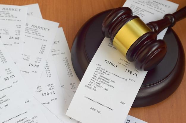 Macete de justiça e muitos recibos de supermercado na mesa de madeira