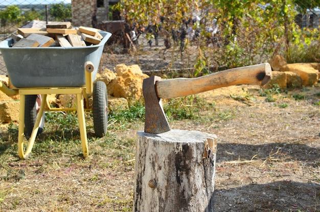 Machado em um tronco de madeira. no fundo, um carrinho de mão com um monte de lenha.