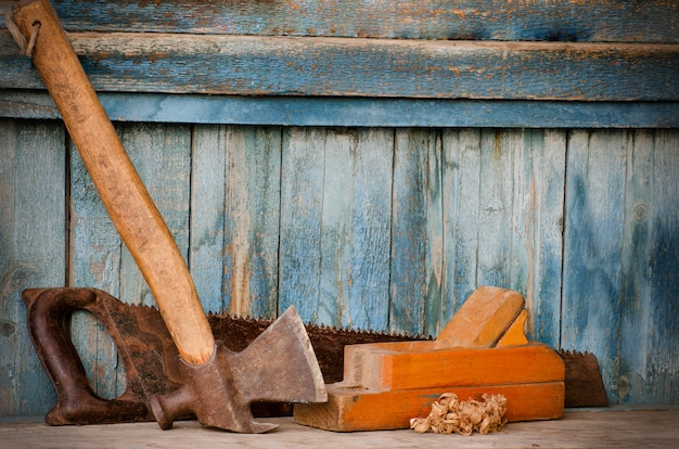 Machado, plaina e serra em uma parede de madeira velha, lascas. espaço para texto
